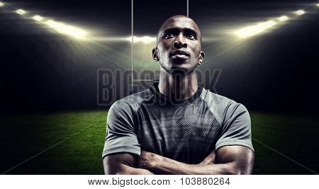 Thoughtful rugby player with arms crossed against rugby stadium