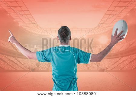 Rugby player gesturing with hands against orange