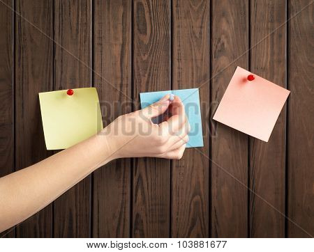 Note Papers With Hand On Wooden Board