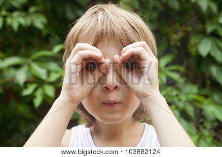 Boy Looking Through Fingers As Binoculars