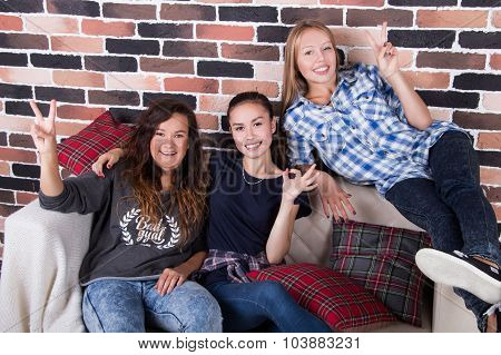 Three Young Beautiful Girlfriends Smilling Sitting On The Couch