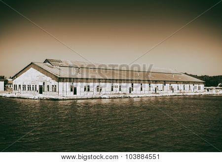 Old Abandoned warehouse on the coast, artistic retro style toned photo