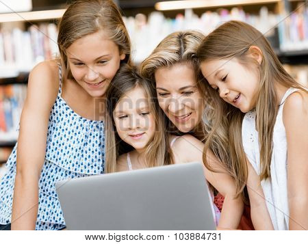 Little girls and mother with a laptop in library