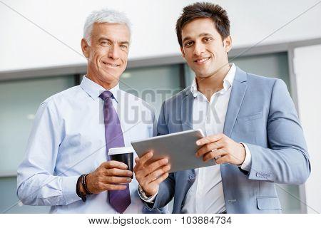 Two businessman in office with devices