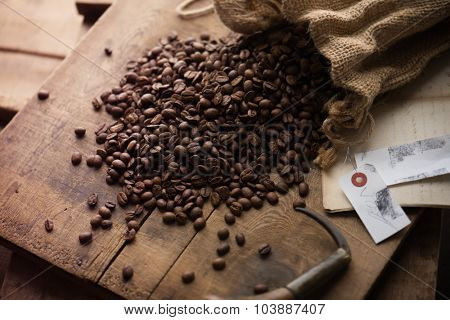 Imported coffee beans spilling out from a hemp sack, on wooden crate lid. shallow depth of field.