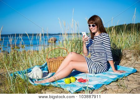 Beautiful Woman With Picnic Basket And Fruits Using Smart Phone On The Beach