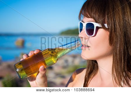 Beautiful Woman Drinking Beer On The Beach