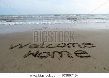 Welcome Home written in sand