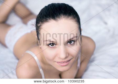 Portrait Of Happy Beautiful Brunett  Girl Lying In A Bed