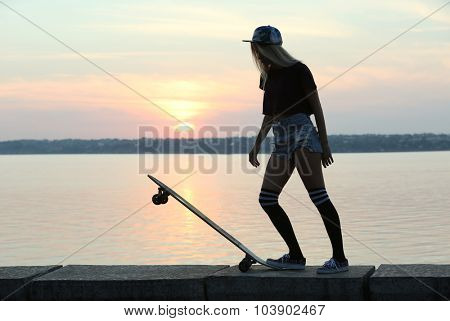 Young woman with skating board on the riverside