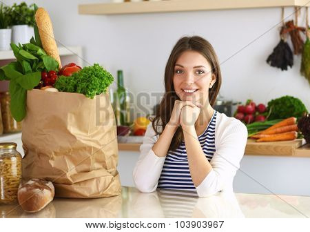 Young woman sitting in kitchen at home