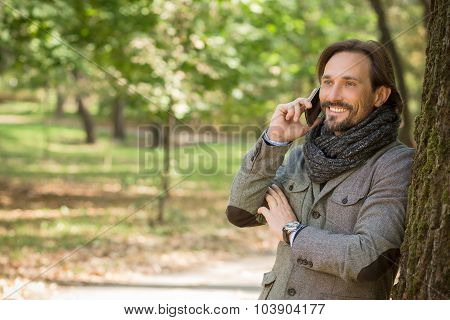 Handsome middle-aged man talking over mobile phone in the park