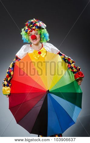 Clown with umbrella in funny concept