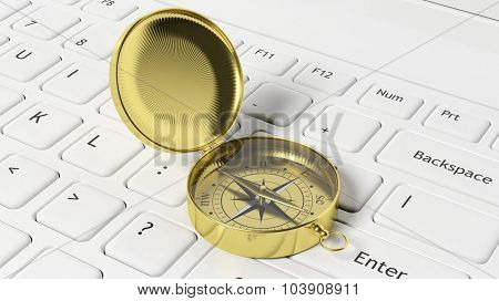 Golden compass on white laptop keyboard