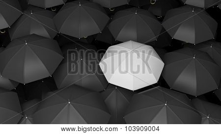 Classic large black umbrellas tops with one white standing out.
