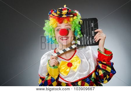 Clown with movie clapper in funny concept