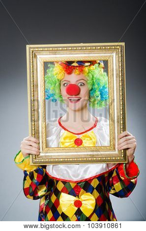 Clown with picture frame in funny concept