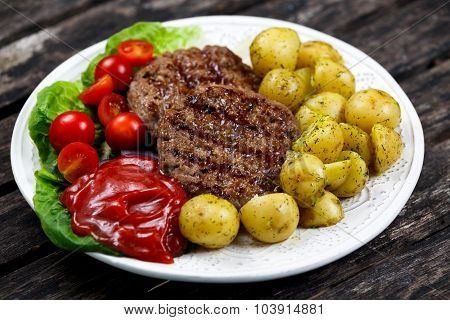 Fresh Juicy Grill Burgers, Served With Ketchup, Young Potatoes, Tomatoes And Vegetables. On Wooden T