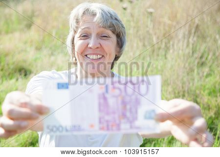 Old age woman holding five hundred euro note