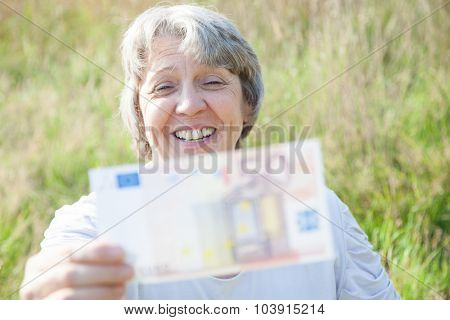 Old age woman holding fifty euro note