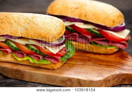 Sandwich With Lettuce, Slices Of Fresh Tomatoes, Cucumber, Red Onion, Salami And Cheese