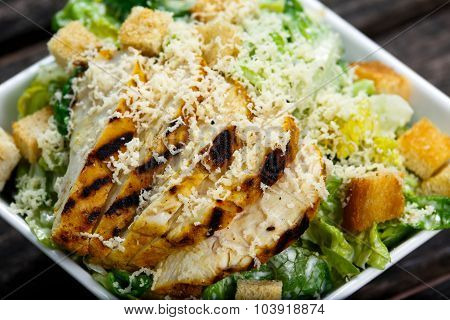Close Up Caesar Salad With Chicken And Lettuce On Wooden Table