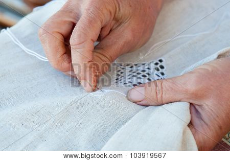 Senior Woman Knitting A White Fabric Cloth