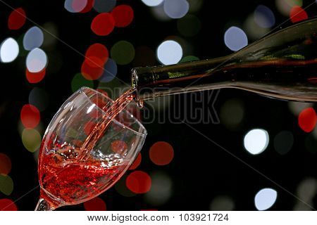 Wine pouring in glass on bright background