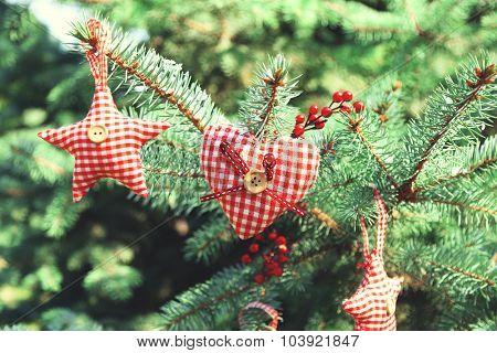 Christmas toys on fir tree branch, outdoors