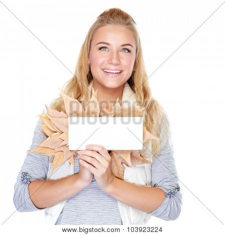 Portrait of beautiful cheerful girl with dry maple leaves isolated on white background, holding in hands blank greeting card, enjoying autumn season