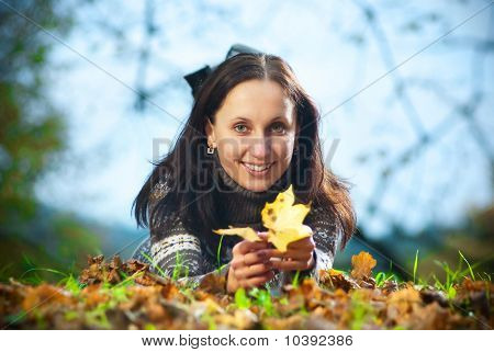smilling woman in autumn park on grass