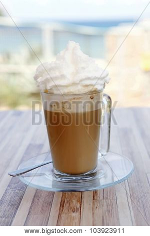 coffee drink with milk cream in mug on wooden table outside