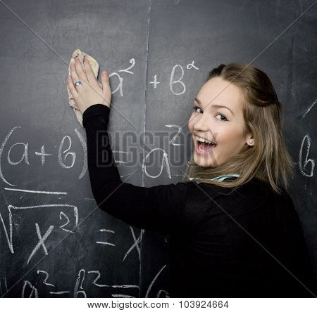 young pretty girl student in classroom at blackboard doing homework