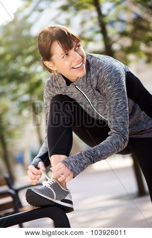 Smiling Sport Woman Tying Shoelace