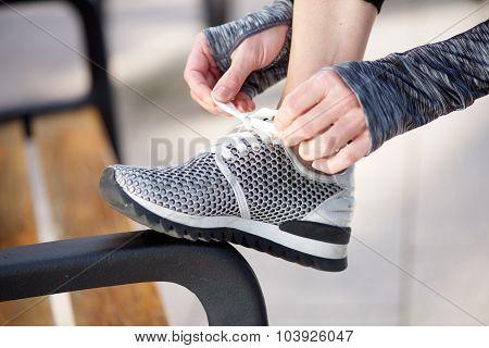 Female hands tying shoelace