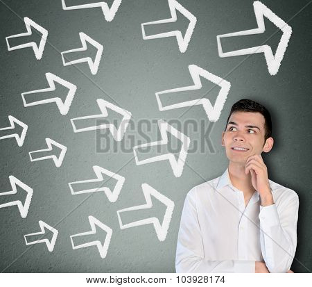 Young business man and arrows pointing right
