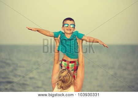 Mother Holding Little Son On Beach Vintage
