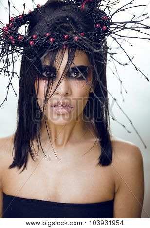 pretty brunette woman with make up like demon at halloween, closeup scary