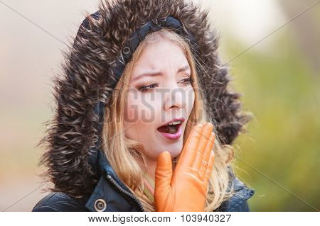 Woman In Hooded Jacket Yawning.