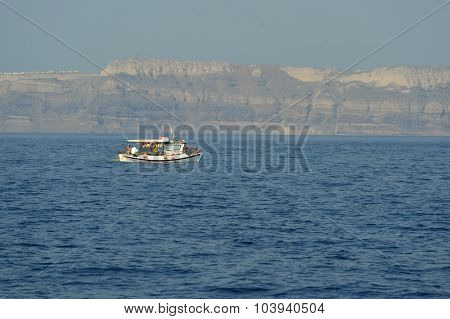 SANTORINI, GREECE - AUGUST 06, 2015: people on boat near Santorini sea coast. Santorini, classically Thera, is an island in the southern Aegean Sea, about 200 km southeast of Greece's mainland.