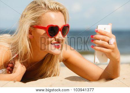 Woman Lying On Sandy Beach Using Cell Phone