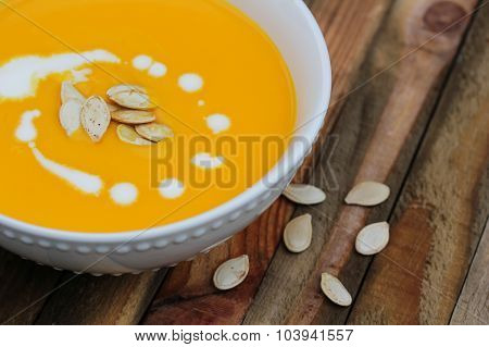 Pumpkin soup served in white bowl on wooden background