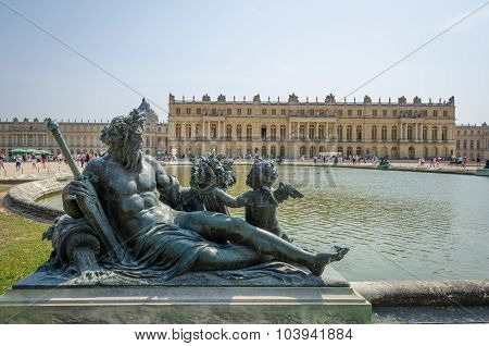 Reclining statue with Palace of Versailles in background