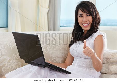 Young Female Using Laptop With Thumb Up