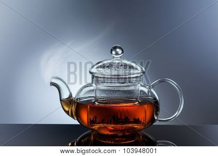 glass teapot cup with hot black tea and steam