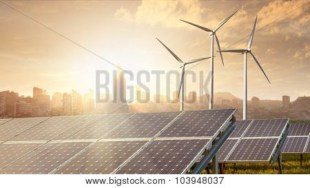 solar panels and wind turbines against city on background under blue sky. Header for website