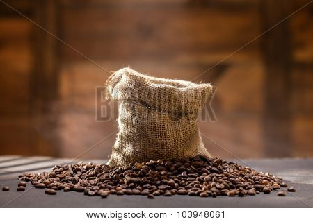 coffee beans with steam in bag on black table against wooden background