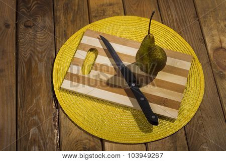 Pear And A Knife Lying On A Cutting Board.