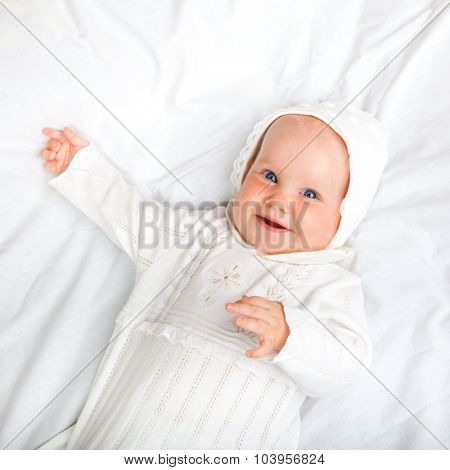 Close-up shot of six month baby girl wearing white christening clothes laying on a bed smiling