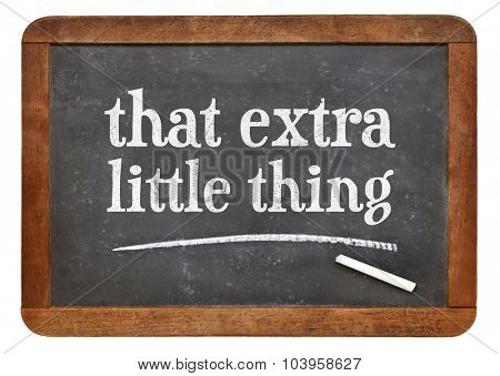 That little extra thing -white chalk text on a vintage slate blackboard